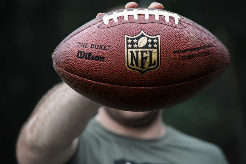 Professional football player holds football to camera